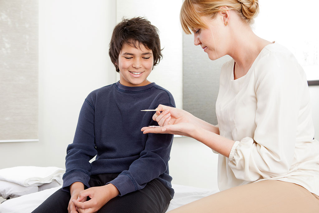 Acupuncturist showing a boy her tools